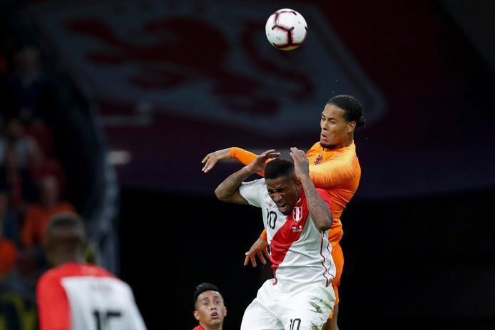 Virgil van Dijk gaat er stevig in tegen Jefferson Farfán van Peru.