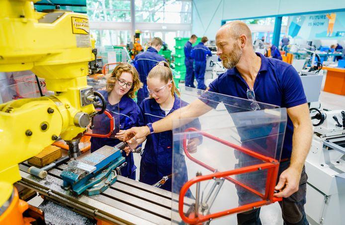Lisa Brama (l) en Femke van der Reep zijn blij dat ze weer met hun handen kunnen werken op school. Docent Jaap van Akkeren ziet dat zijn techniekleerlingen moeten wennen aan het werken met de machines.