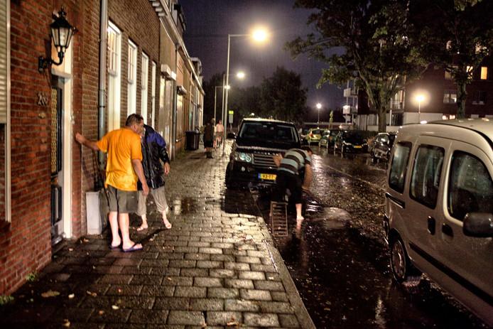 De schade opnemen na een hoosbui in de Boutershemstraat in 2015.