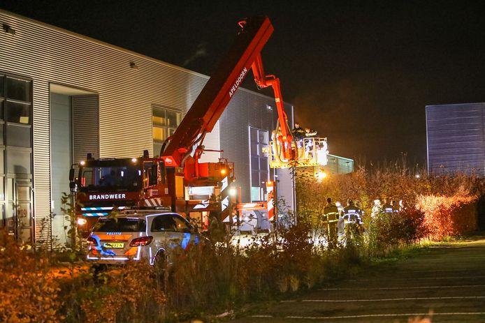 De brandweer en politie aan de Laan van de maagd. De hoogwerker helpt twee agenten en een politiehond het dak op.