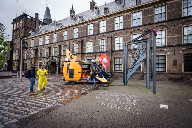 Bij het monument van Willem Drees op de Hofplaats krijten actievoerders de eis van een minimumuurloon van 14 euro op de stoep. Beeld Martijn Beekman