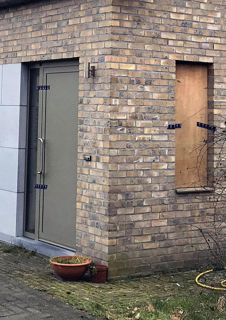 De deur is verzegeld. In het raam dat de politie heeft ingebroken, zit al een paneel.