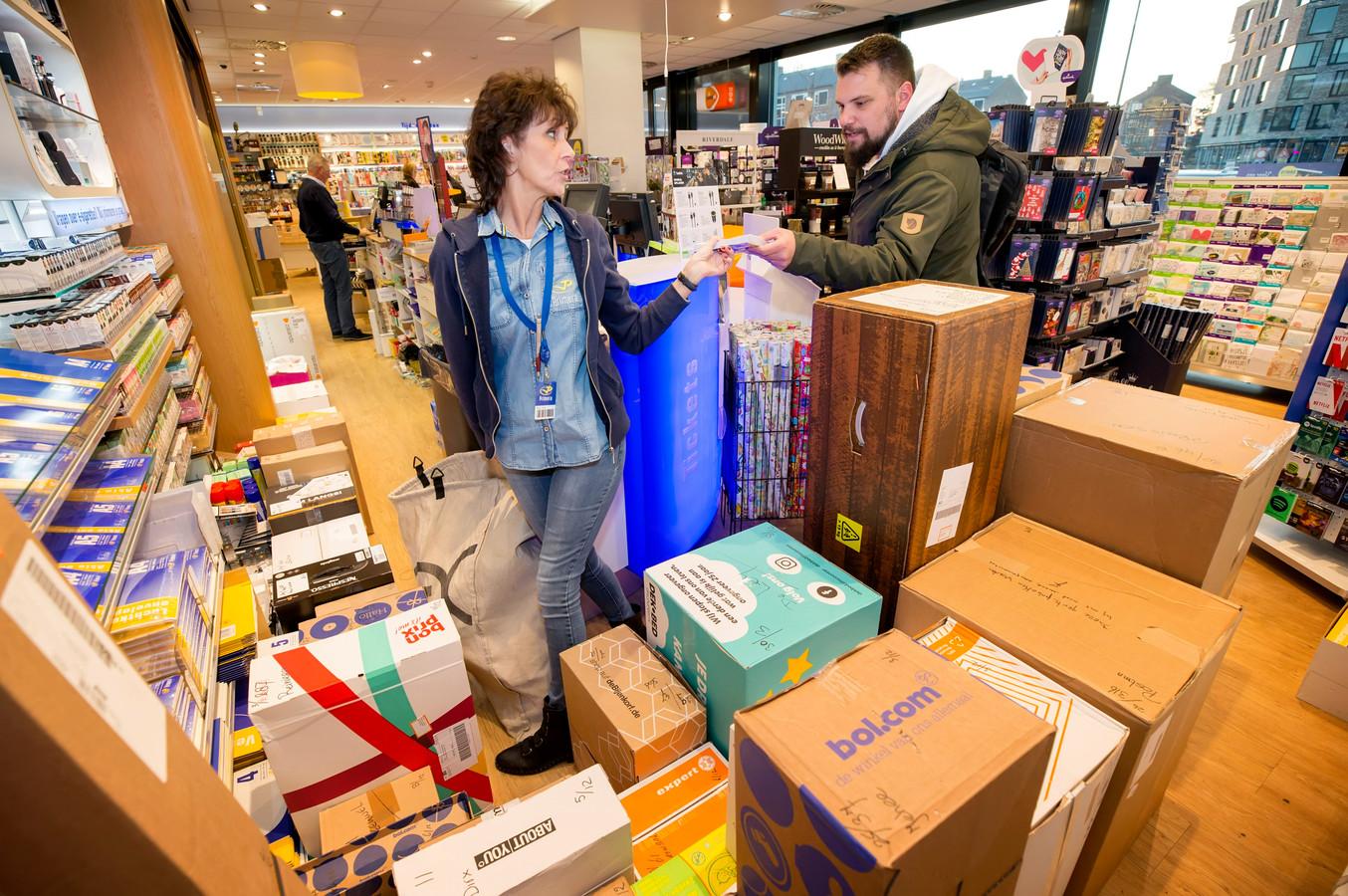 BREDA, Pix4Profs/Joyce van Belkom. Angelica van Dongen helpt een klant in de Primera op het Dr Struyckenplein. DE winkel staat vol met pakketjes.