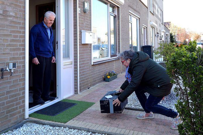 Vrijwilligster Tonneke Bakkeren van Roosendaal voor Elkaar brengt boodschappen bij Jan Melsen.