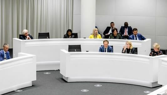 Het college van burgemeester en wethouders met twee lege stoelen tijdens een spoeddebat in de Haagse gemeenteraad over het corruptie-onderzoek naar de wethouders Richard de Mos en Rachid Guernaoui.