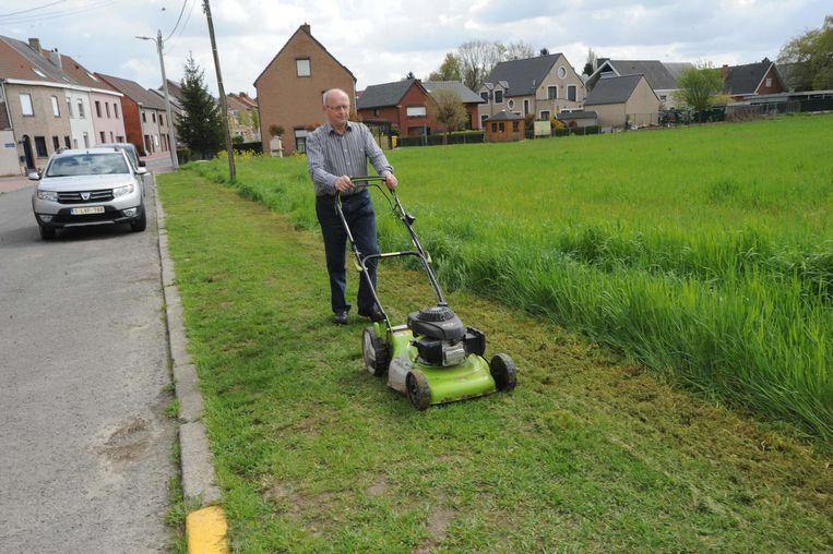 Jos maait het gras op de voetweg zelf.