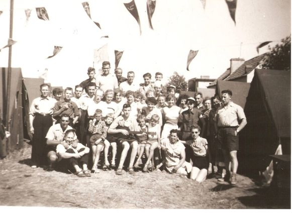 Een van de weinige beelden van Eddy's jeugd, met een gitaar op schoot tussen de kinderen. Hij zong altijd en overal, ook in de jeugdbeweging.