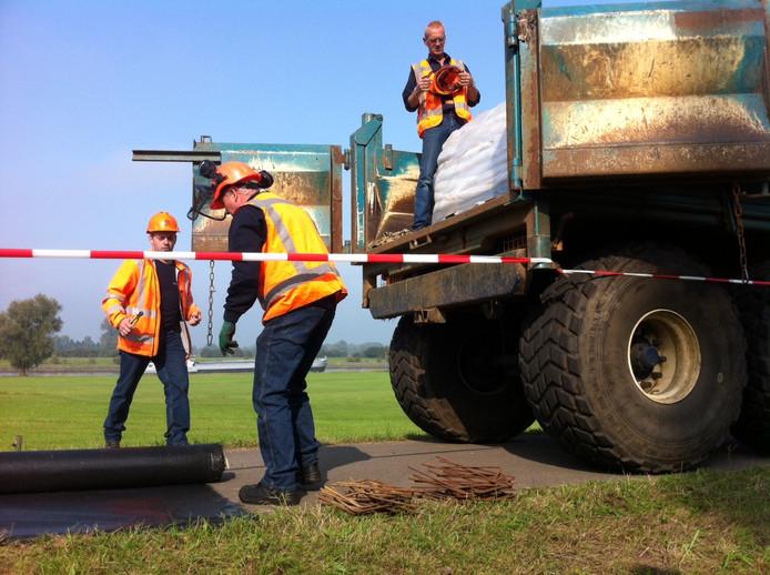 Medewerkers van Waterschap Rijn en IJssel leggen bij Eefde speciaal doek en krammen klaar om op de dijk aan te brengen als noodverband. Met zandzakken erop kan het doek een beschadiging van de dijk opvangen.