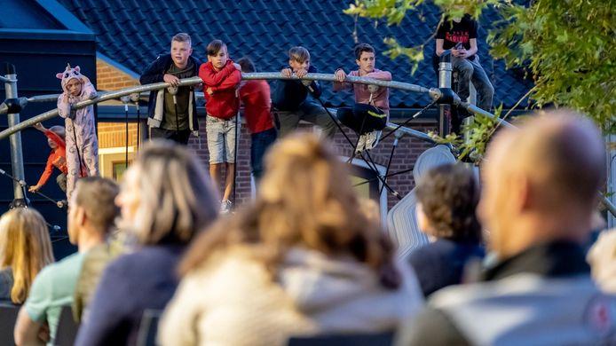 Kinderen volgen vanaf hun schoolplein de openbare dorpsvergadering over hun schoolplein. Hier is een hek gepland om de veiligheid te bevorderen.