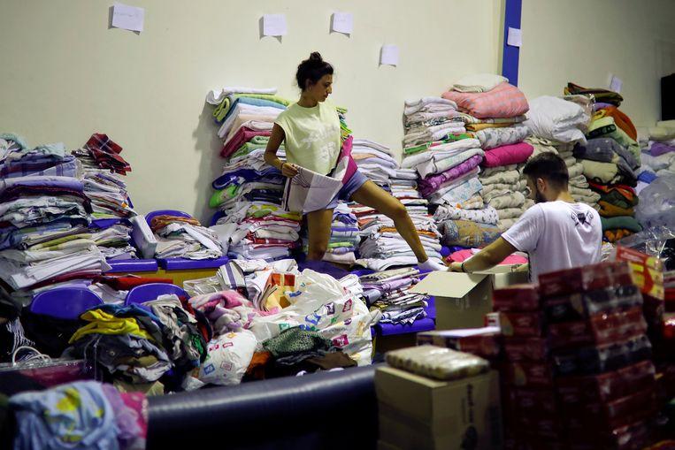 Vrijwilligers ordenen kleding  die bestemd is voor slachtoffers van de getroffen dorpen in Nea Makri. Beeld Alkis Konstantinidis, Reuters