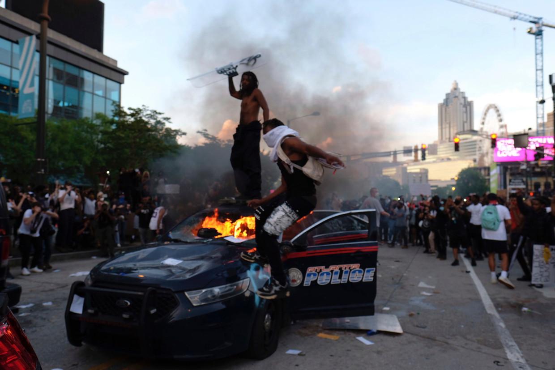 Demonstranten in Atlanta bestormden het hoofdkantoor van de tv-zender CNN, vernielden een politie-auto en staken die in brand. Beeld AP
