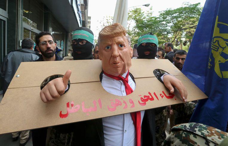 Een als president Trump vermomde betoger heeft zich in een kartonnen schandpaal gestoken. Beeld AFP