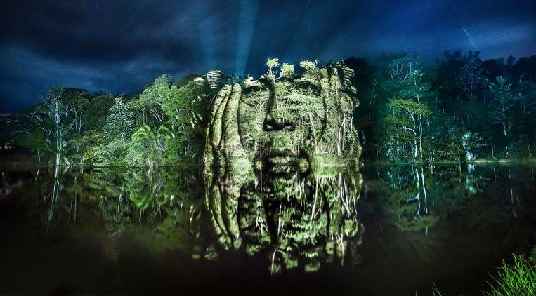 De Franse kunstenaar Philippe Echaroux projecteerde in 2017 portretten van indianen in de Braziliaanse jungle om aandacht te vragen voor toenemende ontbossing in het Amazonegebied.   Beeld Getty