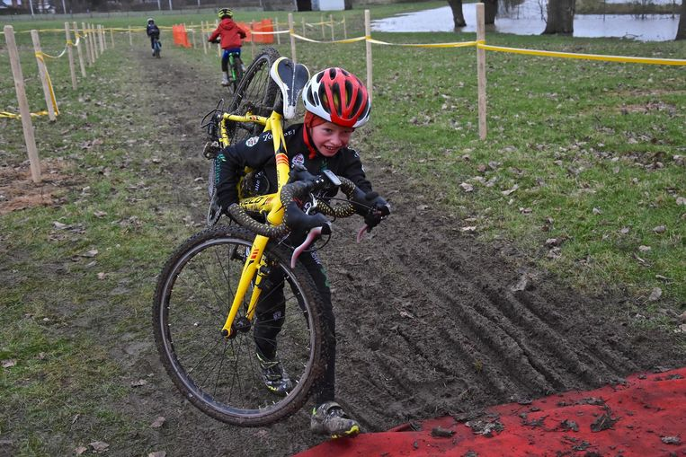 Deze jonge renner loopt met zijn fiets de helling op, zo kan hij alvast niet uitglijden in de modder.
