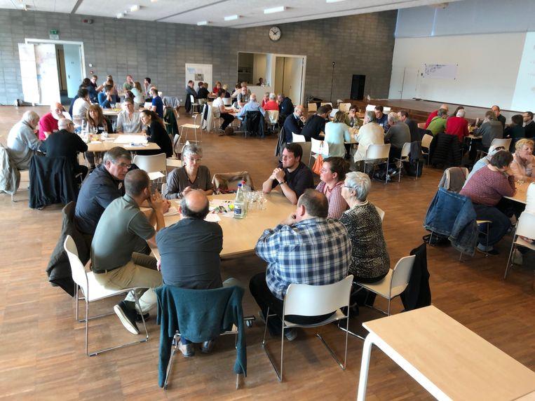 Mensen praten met elkaar over hun ideeën om van Mortsel een betere stad te maken tijdens de Toekomstdag in de Parkschool.