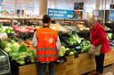De vakkenvullers van de supermarkten krijgen speciale hesjes met een duidelijke tekst op de achterkant: 'hou voldoende afstand.'