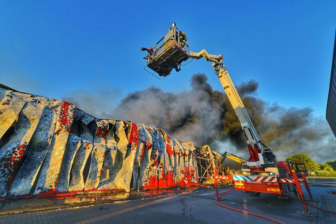 De resten van het pand van Van der Heijden Transport in Hapert, een dag na de brand.
