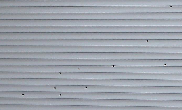 Het raam was afgesloten met een rolluik. Dat is doorzeefd met kogels.