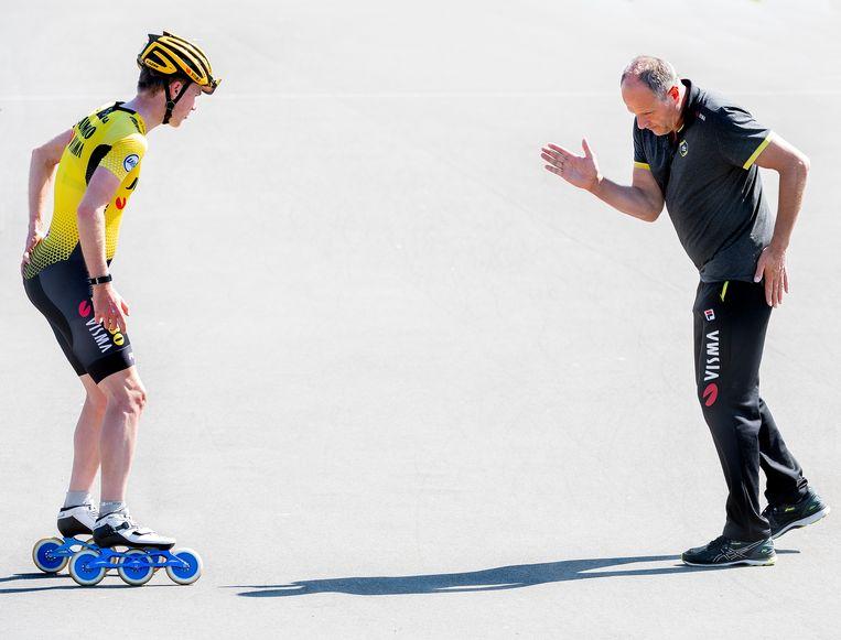 Jac Orie, de coach van de Jumbo-Visma schaatsploeg, geeft tijdens de training van de schaatsploeg op de skeelerbaan van Wolvega, op gepaste afstand aanwijzingen aan Kars Jansman. Beeld Klaas Jan van der Weij