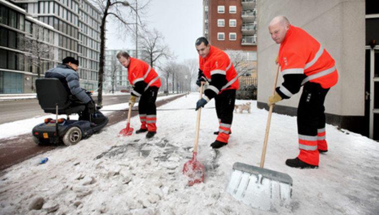 Een team van de Amsterdamse gemeentereiniging schept sneeuw en ijs weg op voetpaden zoals hier bij het Flevohuis aan de Zeeburgerdijk. Foto Jean-Pierre Jans Beeld
