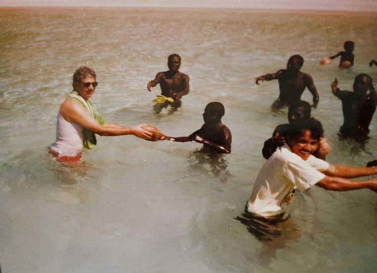 In 1991 brachten T.N. Pandit (links) en metgezellen een bezoek aan het eiland Noord-Sentinel, waarbij ze kokosnoten aan de bewoners overhandigden. Beeld The New York Times