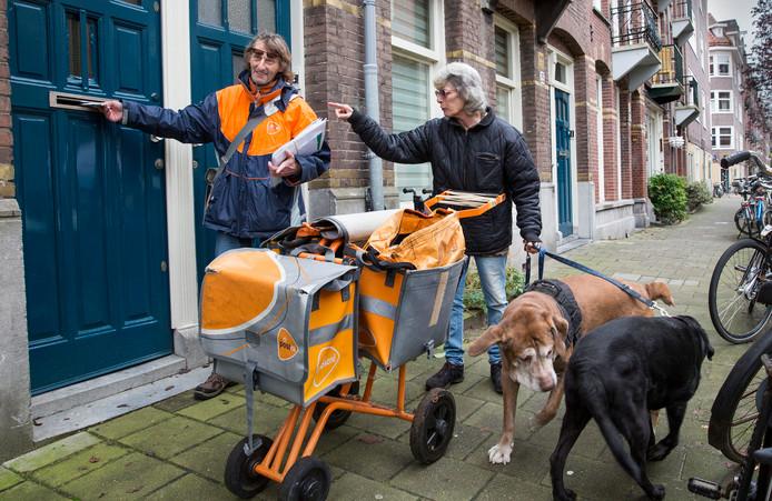 Een Amsterdamse bezorger maakt een praatje met een buurtbewoner. Het personeel van PostNL kan een nuttige functie in de wijk vervullen
