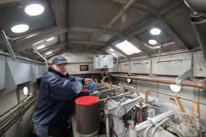 De eigenaar van de sleepboot Laura controleert de temperatuur van de motor en hanteert de oliespuit.