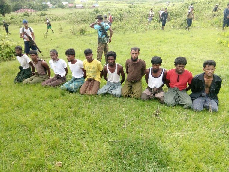 Tien Rohingya's zitten in september 2017 geknield. Ze worden in de gaten gehouden door leden van de Myanmarese veiligheidsdiensten. Beeld REUTERS