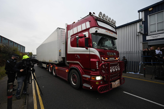 De vrachtwagen waarin de 39 lichamen werden gevonden, wordt door agenten weggereden.