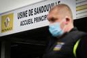 Een medewerker van Renault met mondkapje bij de ingang van de autofabriek in Sandouville, bij Le Havre, die vandaag voor het eerst weer operationeel is