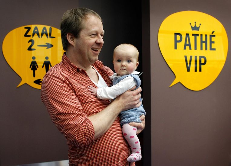 Een vader gaat met zijn baby naar de film. Beeld null