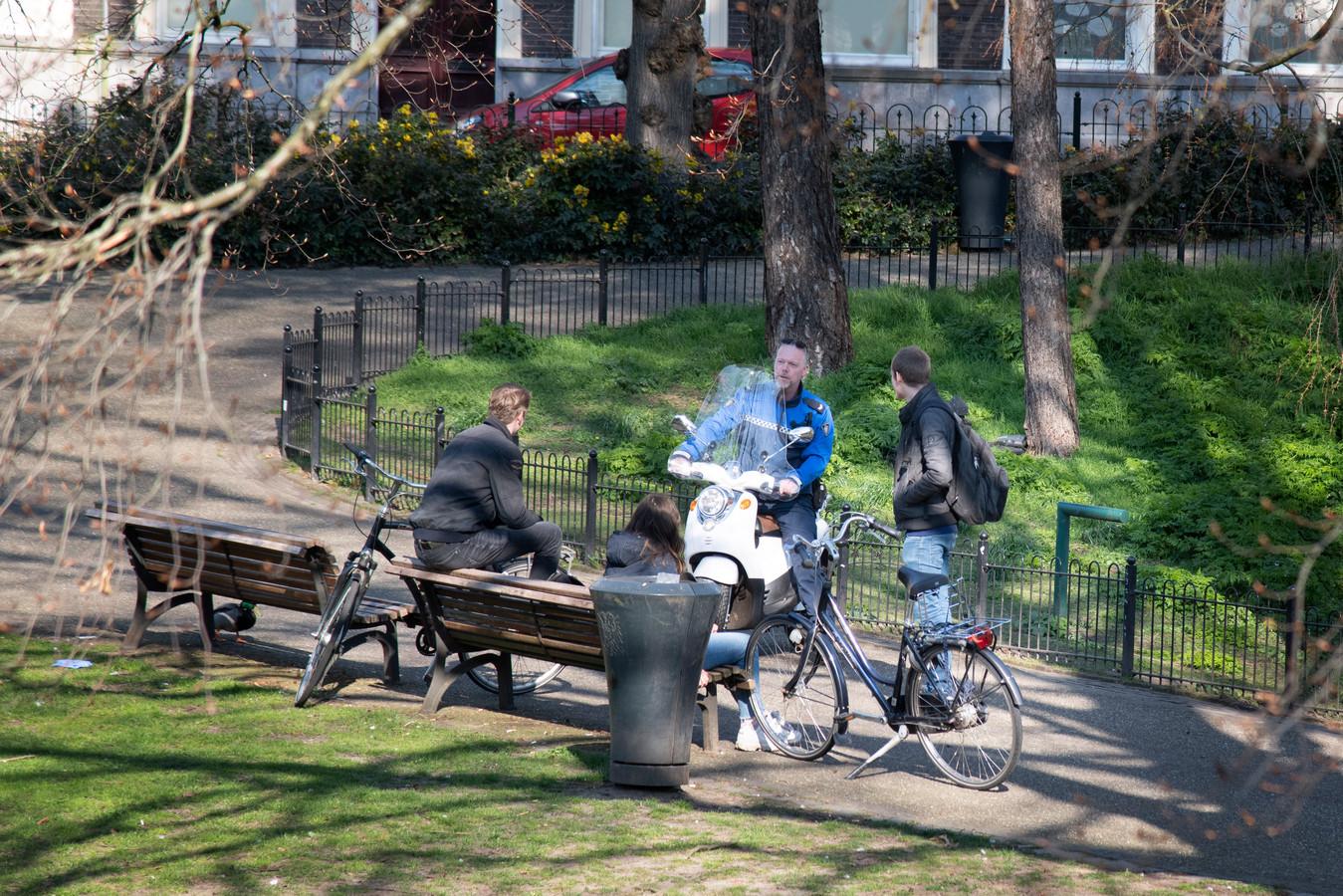 Een gemeentelijke handhaver spreekt donderdagmiddag jongeren aan in het Kronenburgerpark. Zij overtreden de coronamaatregel om 1,5 meter afstand te houden.