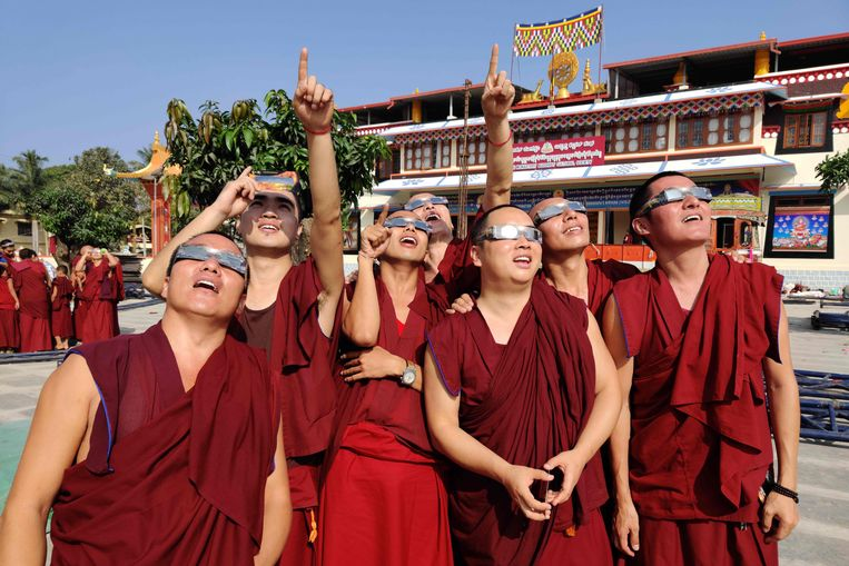 Monniken van een Tibetaans klooster in Teginkoppa in India bekijken de eclips door een beschermende bril.