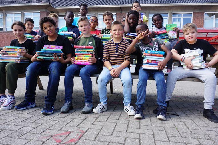 Enkele kinderen van de lagere school van het Atheneum Denderleeuw poseren fier met de nieuwe boeken.