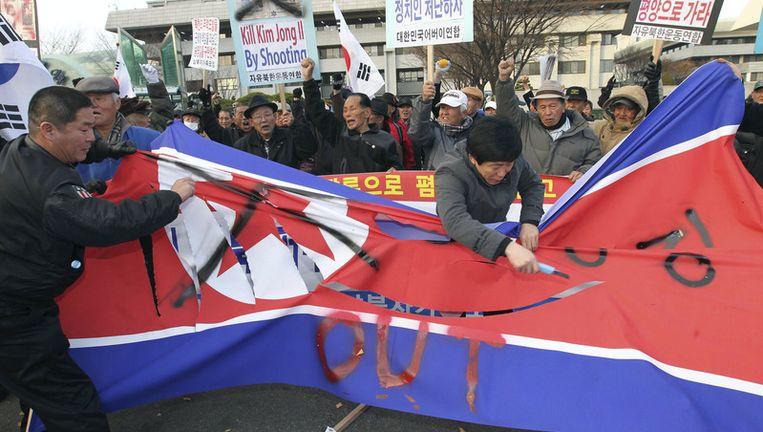 Zuid-Koreanen snijden een Noord-Koreaanse vlag aan stukken als teken van het protest tegen de bombardementen Beeld ap
