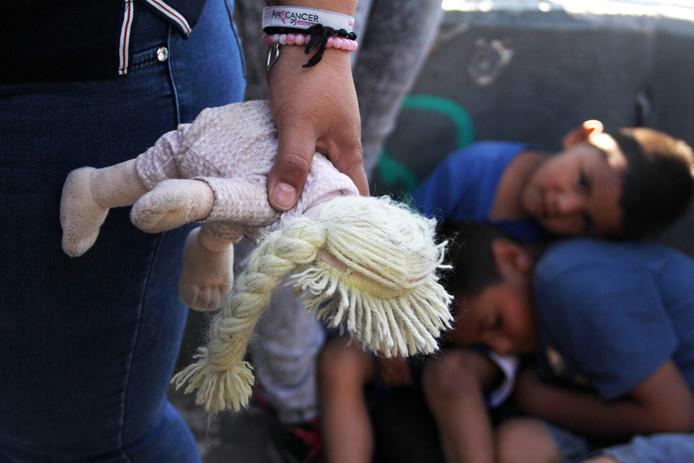 Een vrouw draagt een popje mee bij de Mexicaans-Amerikaanse grens.