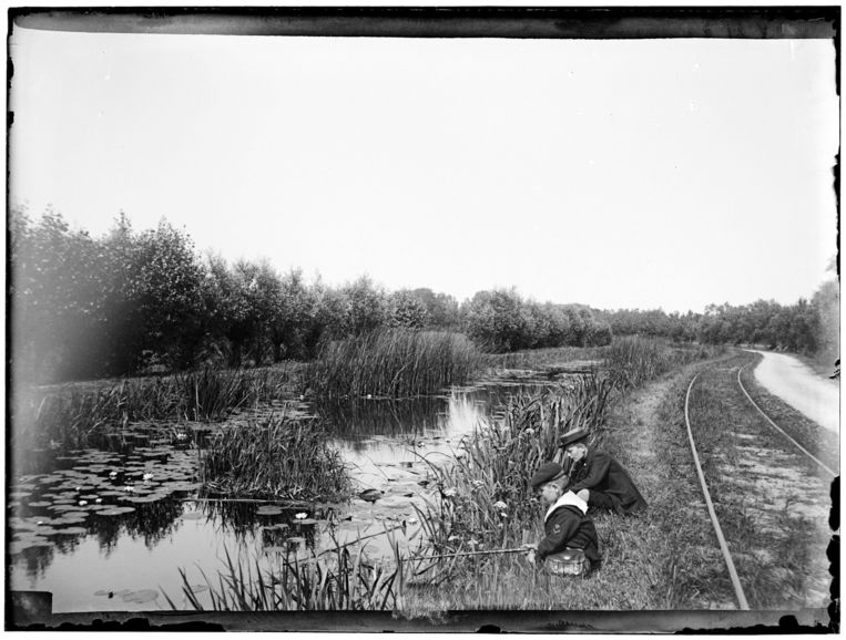 Jongens vissen in de buurt van Muiderberg, voor het spoor van de Gooische Stoomtram Maatschappij, in 1898.   Beeld Stadsarchief Amsterdam / B.W. Stomps