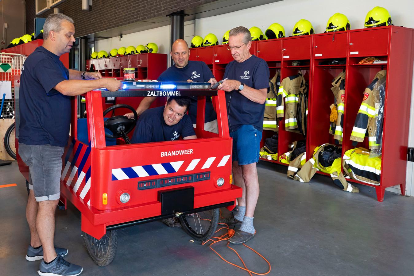 De mannen van de brandweer bouwen een zeepkist voor de wedstrijd tijdens de Bommelweek.