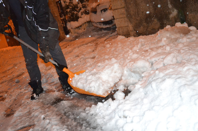 Een man schuift een dikke laag sneeuw weg in Saint-Jean Bonnefonds bij Saint-Étienne.