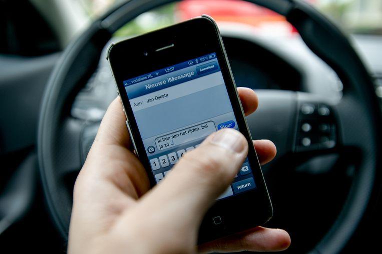 Een automobilist verstuurt een sms. Beeld null