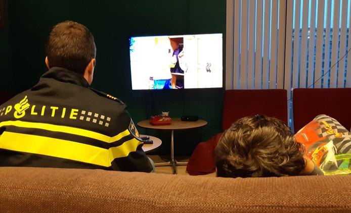 De weggelopen peuter kijkt televisie met de politie.