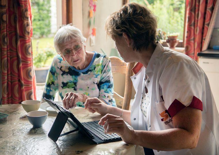 Een thuiszorgverpleegkundige helpt een nog thuiswonende oudere dame met beginnende dementie. Beeld Hollandse Hoogte / Frank Muller / Zorginbeeld