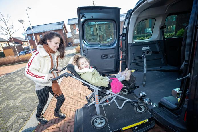 Lotte duwt haar dochter Pip met stoel en al de auto in.