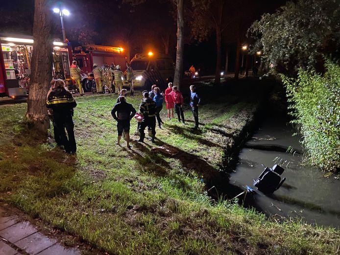 De scootmobiel ligt nog in het water. De man wordt in de ambulance geholpen.