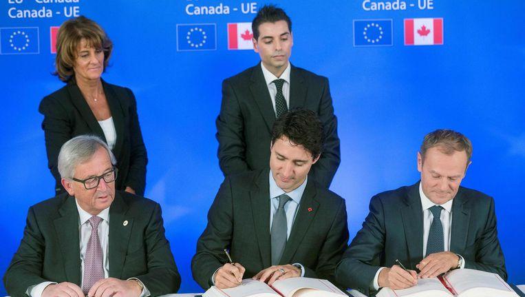 De Canadese president Trudeau (midden) en Europese leiders Jean-Claude Juncker (links) en Donald Tusk (rechts) tekenen het Ceta-verdrag. Beeld afp