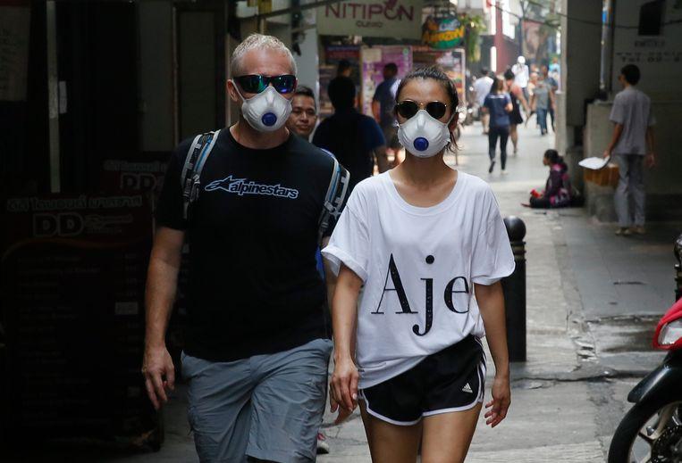Toeristen dragen gezichtsmaskers terwijl ze door Bangkok lopen.
