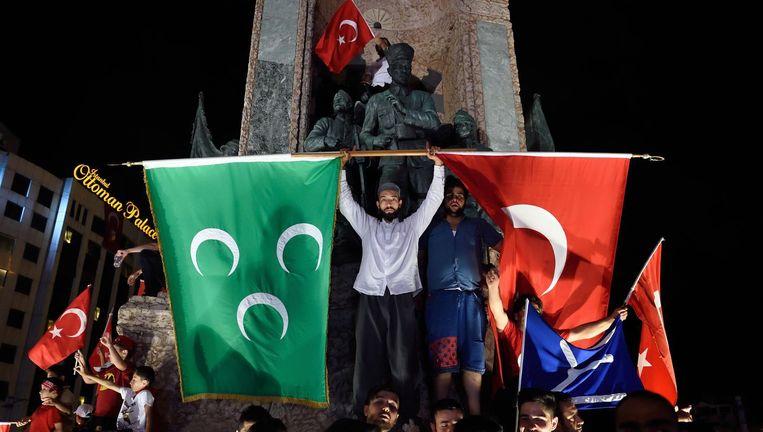 Erdogan-aanhangers met Turkse (rechts) en Ottomaanse (links) vlag op het Taksimplein in Istanbul, 20 juli. Beeld afp