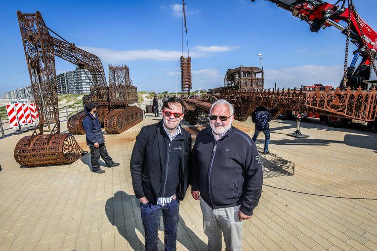 Kunstenaar Wim Delvoye en burgemeester Jean-Marie Dedecker poseren bij de kunstwerken.