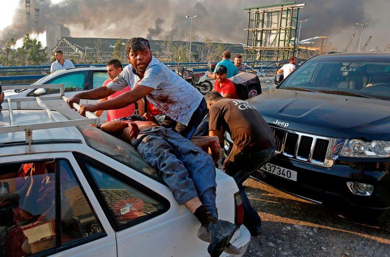 Een man ligt gewond op de motorkap van een auto na de enorme explosie in het havengebied.   Beeld AFP