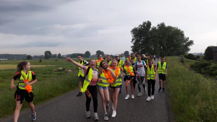 Deelnemers van een van de voorgaande edities van de Bommelerwaardse Avondvierdaagse op de dijk bij Hoenzadriel.